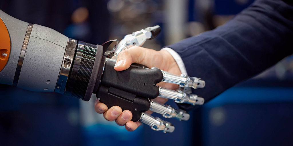 A robot shaking hands with a man