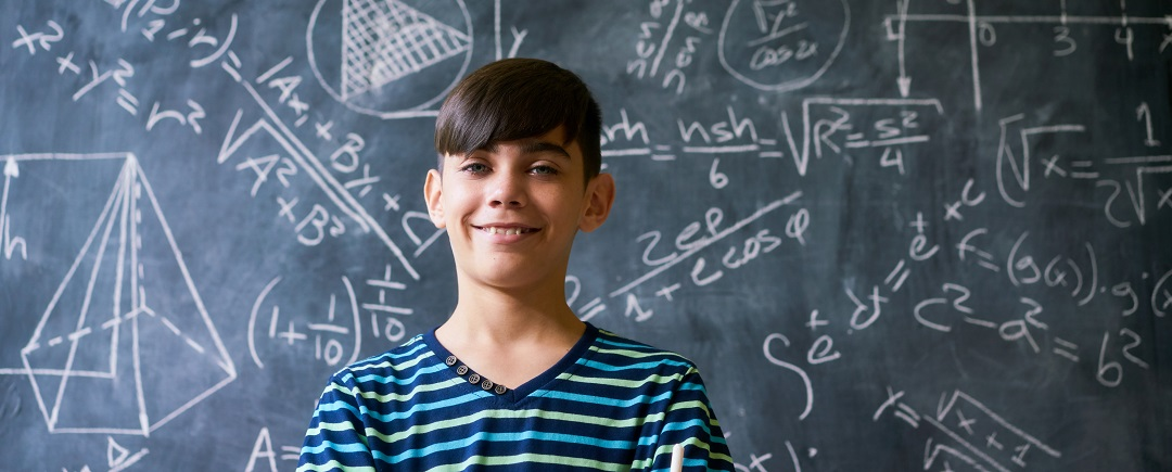 Concept on blackboard at school. Young people, student and pupil in classroom. Smart hispanic boy writing math formula on board during lesson. Portrait of male child smiling, looking at camera smart Timico